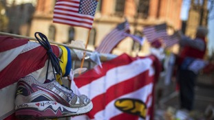 A trainer is seen at a makeshift memorial in Boston