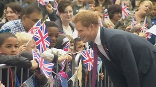 Prince Harry shares a joke with children outside the new Headway HQ.