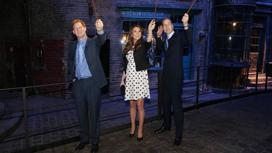 Prince Harry, the Duchess and Duke of Cambridge raise their wands.