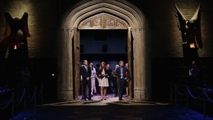 The Duke and Duchess of Cambridge with Prince Harry walk through the set used to depict Hogwart's 'Great Hall'.