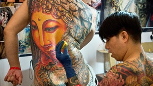 A professional tattoo artist gets to work at the International Tattoo Convention in Germany