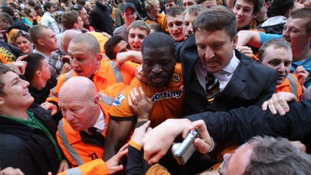 Wolverhampton Wanderers' George Elokobi is helped off the pitch after the final whistle as fans invade as the club survives relegation