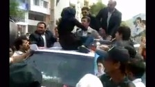 A women sits on Iranian President Ahmadinejad's vehicle to tell him about her economic conditions