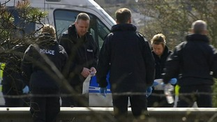 Forensic teams  search the carriageway yesterday