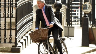 Andrew Mitchell rides his bicycle around Westminster