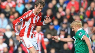 Stoke City's Peter Crouch and Norwich City's Zak Whitbread (right) battle for the ball