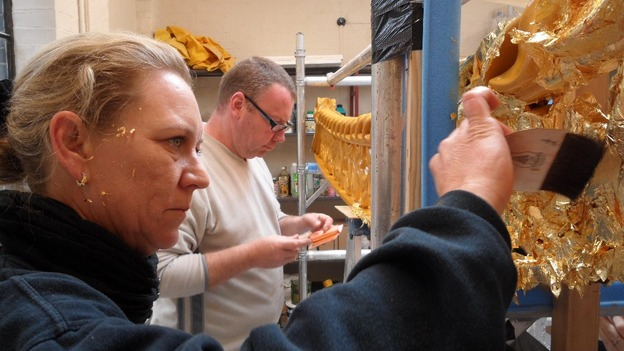 Craftsmen apply gold leaf.