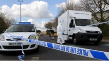 Forensic police officers examine evidence at the crime scene where two men escaped from a prison van that came under attack in Salford