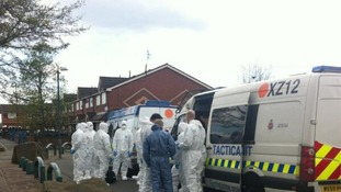 Forensic officers and Tactical Aid Units gather on an estate in Ordsall.