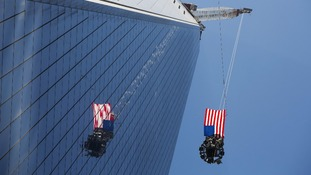 US flag flutters in the wind as the final piece of a spire is lifted above New York