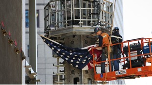 Ground Zero workers attach a US flag t the spire