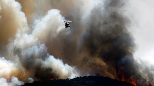 A water-dropping helicopter makes a drop on a fast moving bush fire