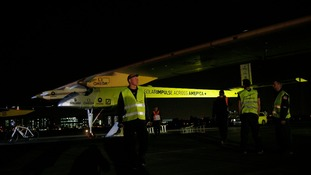 Solar Impulse crew members stand next to their sun-powered aircraft on the runway before take-off