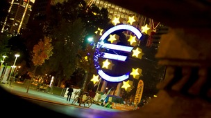 The Euro sculpture is seen behind a fountain statue at Willy-Brandt-Platz in Frankfurt.