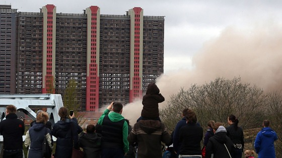 Onlookers watch as the high-rise is transformed into a cloud of smoke and rubble.