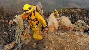 Firefighters make their way out of a canyon as they battle the Springs Fire near Malibu, California.