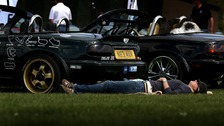 A woman relaxes in the sun at a car show held at Imperial War Museum Duxford in Cambridgeshire