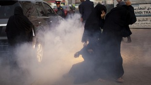 Police use a stun grenade during an anti-government rally in Manama