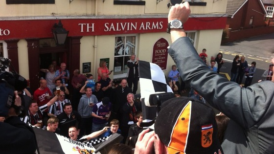 Crowds welcome Spennymoor Town FC victory bus.