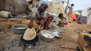 A girl living in an internally displaced camp south of Mogadishu cooks bread on May 3, 2013.