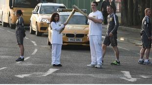 Jasmine Vanmali and Samuel Rowbotham holding the torch