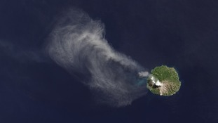 The satellite detected a white cloud of smoke and ash drifting northwest over the sea
