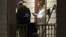 FBI agents search the home where three women were found alive yesterday.
