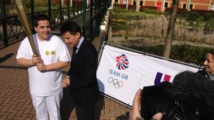 Man holding torch with Lord Coe