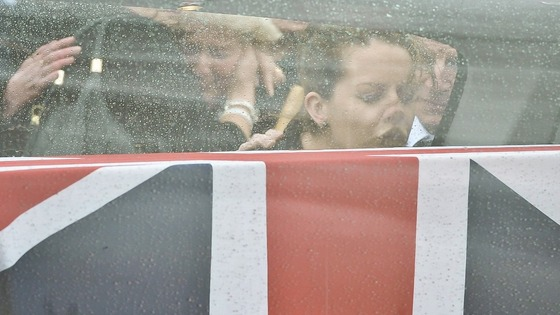Lyndsey Savage, the wife of Cpl William Savage touches the glass side of the hearse