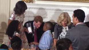 Prince Harry watches as children make presents for their mothers at the White House.