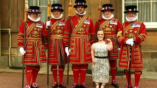 Paralympic swimmer Ellie Simmonds with members of the Yeoman of the Guards after receiving her OBE.