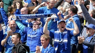 Leicester City fans celebrate their first goal in the stands