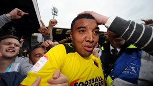 Watford's Troy Deeney is mobbed by fans on the pitch