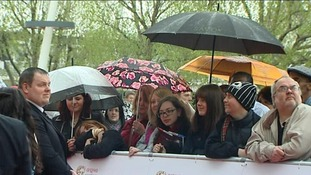 Members of the public dressed in wet weather gear wait patiently for the arrival of actors at BAFTA Awards