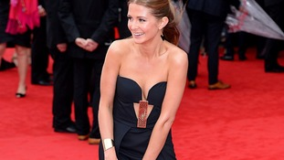 Actress Millie Mackintosh is forced to hold her dress down on the red carpet