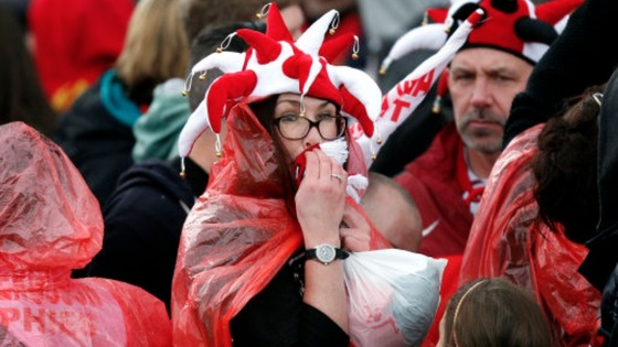 A Manchester United wipes rain from her face as she waits for the Parade to begin