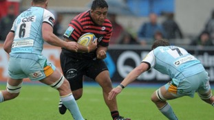 Saracens' Mako Vunipola is tackled by Northampton Saints' Calum Clark and Tom Wood