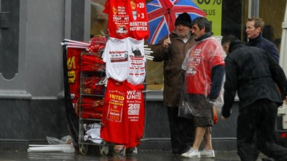 A stall holder sells Manchester United related Merchandise as rain pours down