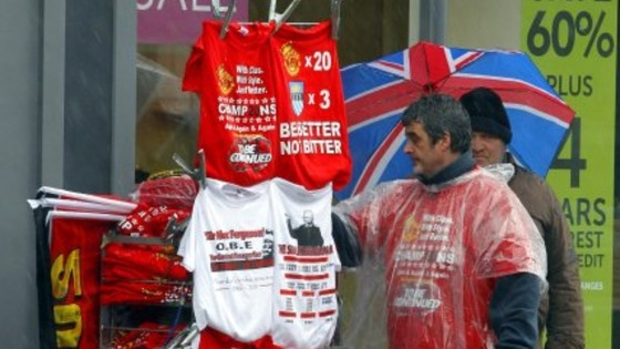A stall holder sells Manchester United related Merchandise as rain pours down ahead of the Premier League winners parade through Manchester.