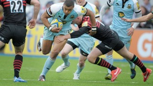 Northampton's Luther Burrell is tackled by Saracens' Owen Farrell