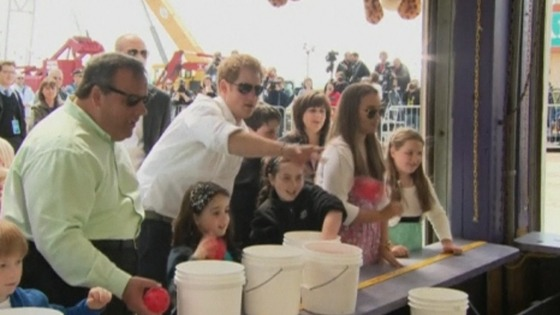 Prince Harry flings a coloured ball at a target in an amusement arcade at Jersey Shore
