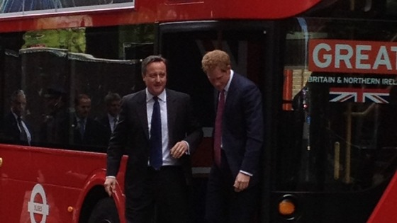 David Cameron and Prince Harry emerge from the Routemaster