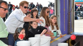 Prince Harry tries his hand at a fairground stall in Mantoloking, a borough of Ocean Heights, New Jersey