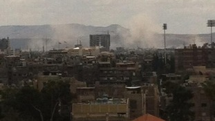 Smoke rises from two hits after a MiG airstrike in Damascus.