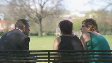 Man on park bench chats to 2 women seen from behind