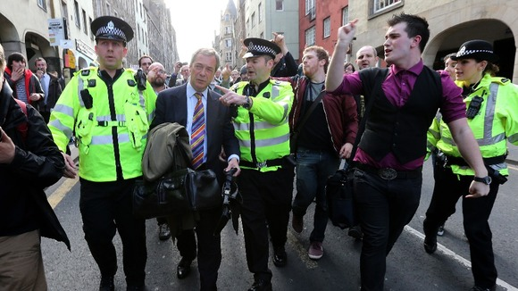 Police escort Nigel Farage into riot van after pub protest
