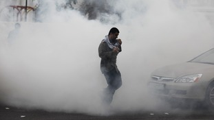 A demonstrator runs through a cloud of tear gas fired by police during a protest in the village of Diraz, west of Manama.