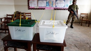 An army soldier guards ballot boxes inside a polling station.