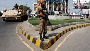 An army soldier stands guard on a road leading to a polling station in Karachi.
