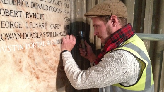 Craftsman Benn Swinfield carefully carves Archbishop Justin Welby's name